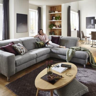 Frau sitz auf gemütlicher Eck-Couch mit Relaxfunktion