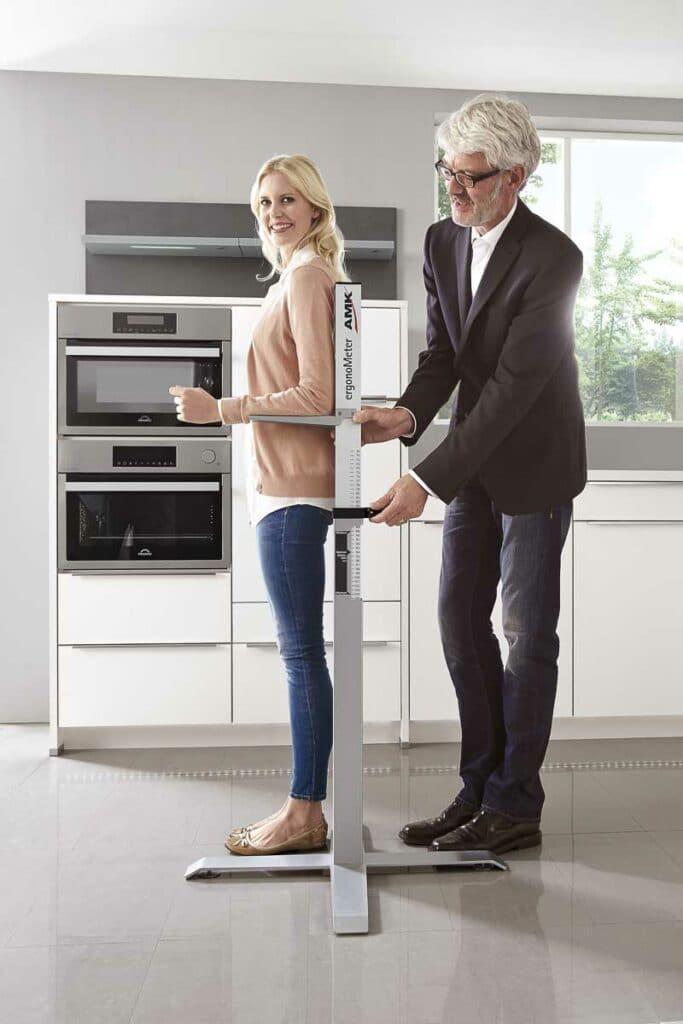 Küchenkäuferin wird für ideale Körpergröße mit Ergometer ausgemessen. Im Hintergrund ein Backofen auf Augenhöhe